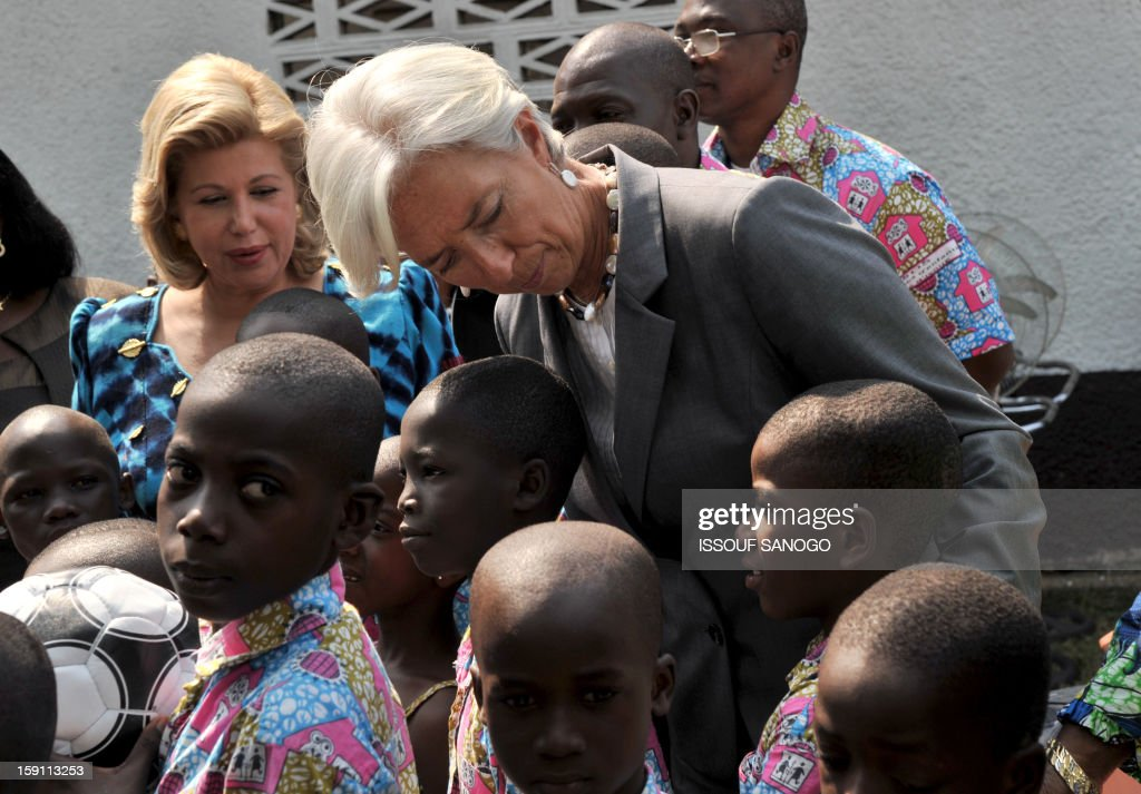 The chief of the International Monetary Fund, Christine Lagarde (C) and Ivory Coast first lady Dominique Ouattara (L) visit an orphanage village in Abobo, suburb of Abidjan on January 8, 2013. Lagarde, called for 'a second Ivorian economic miracle' during a visit to Abidjan as part of an African tour. AFP PHOTO / ISSOUF SANOGO