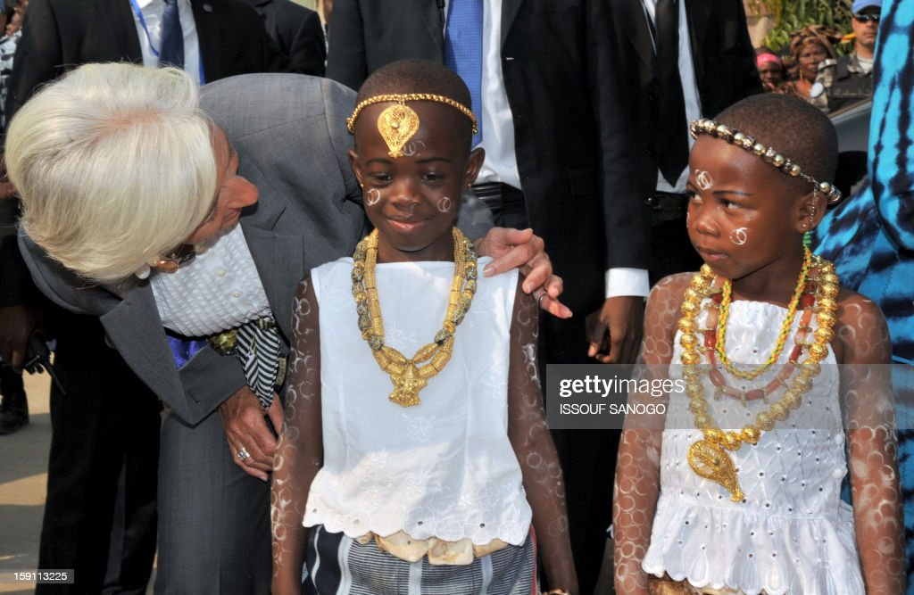 The chief of the International Monetary Fund, Christine Lagarde (L) is welcomed by girls at the SOS village suburb of Abidjan on January 8, 2013. Lagarde, called for 'a second Ivorian economic miracle' during a visit to Abidjan as part of an African tour.