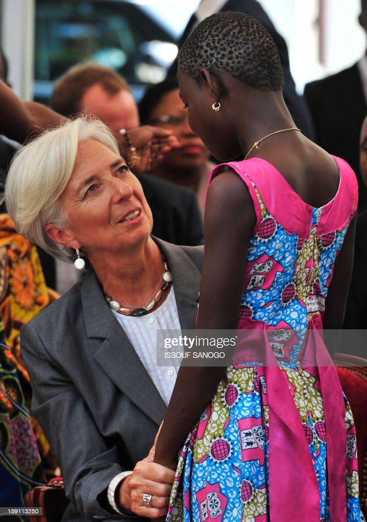 The chief of the International Monetary Fund, Christine Lagarde (L) speaks with a girl as she visits an orphanage village in Abobo, suburb of Abidjan on January 8, 2013. Lagarde, called for 'a second Ivorian economic miracle' during a visit to Abidjan as part of an African tour. AFP PHOTO / ISSOUF SANOGO