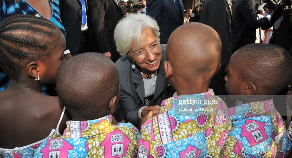 The chief of the International Monetary Fund, Christine Lagarde (C)visit an orphanage village in Abobo, suburb of Abidjan on January 8, 2013. Lagarde, called for 'a second Ivorian economic miracle' during a visit to Abidjan as part of an African tour.