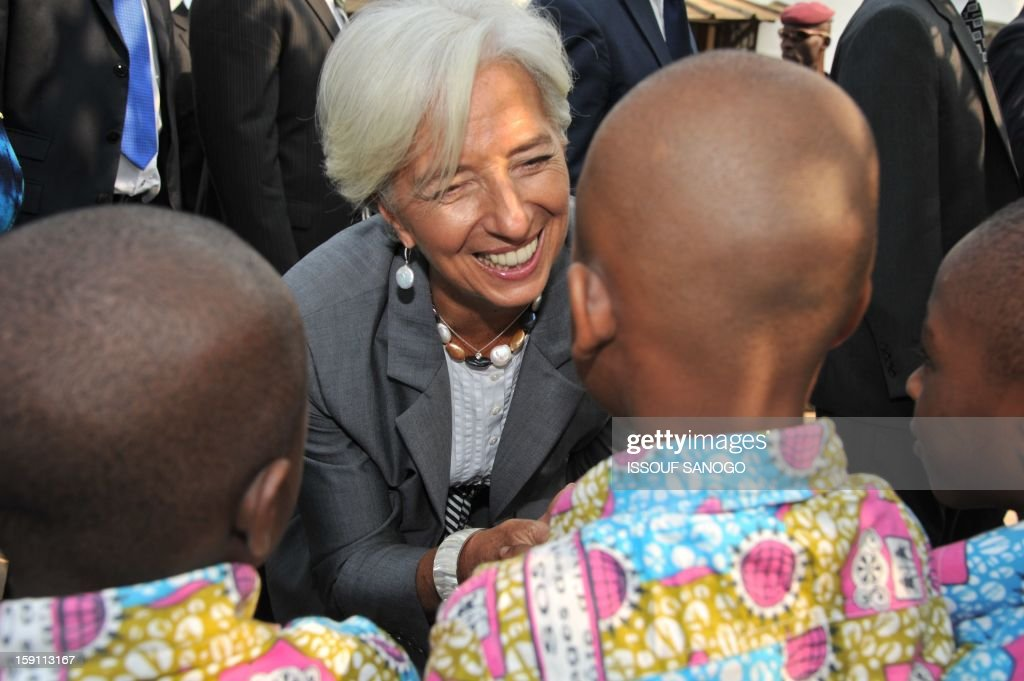 The chief of the International Monetary Fund, Christine Lagarde (C) visits an orphanage village in Abobo, suburb of Abidjan on January 8, 2013. Lagarde, called for 'a second Ivorian economic miracle' during a visit to Abidjan as part of an African tour.