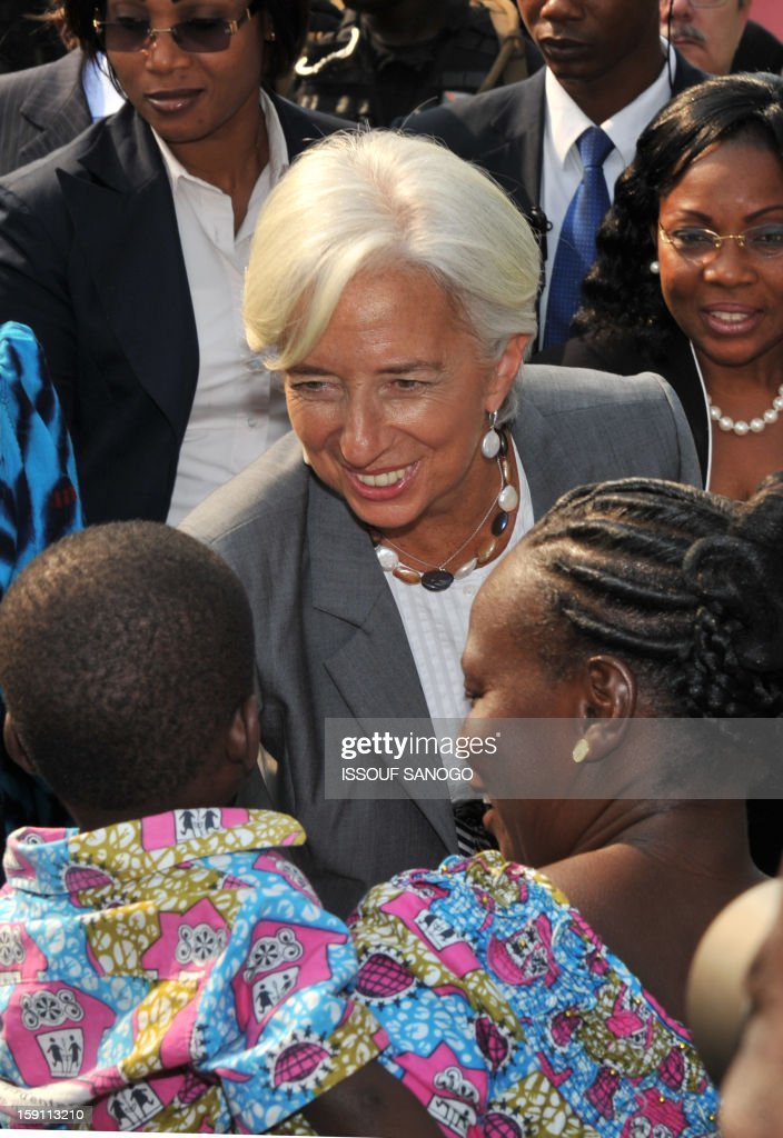 The chief of the International Monetary Fund, Christine Lagarde (C) visits an orphanage village in Abobo, suburb of Abidjan on January 8, 2013. Lagarde, called for 'a second Ivorian economic miracle' during a visit to Abidjan as part of an African tour. AFP PHOTO / ISSOUF SANOGO