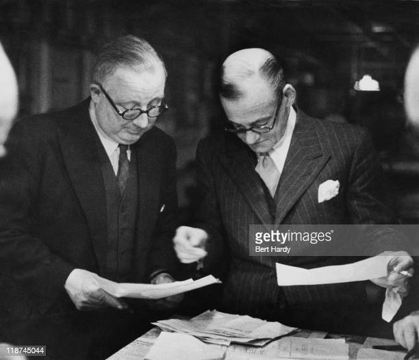 The chief printer consults with the works manager on a Saturday afternoon at the offices of the News of The World April 1953 Original Publication...