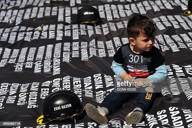 The child of a slain miner sits on April 13 2015 on a list bearing the names of the 301 killed miners last year at a special tribunal set up in a...