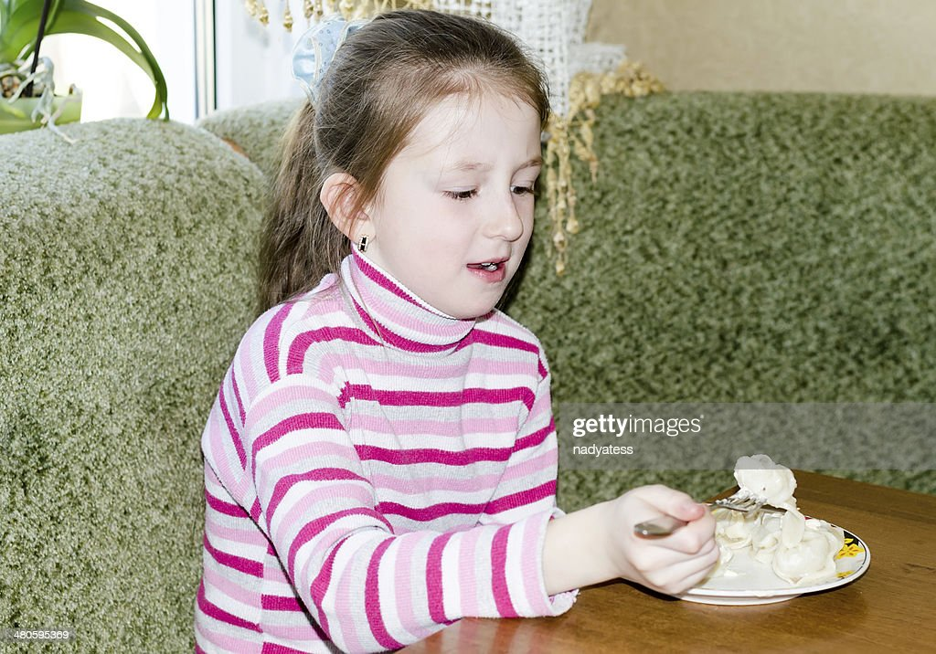 the child, the girl eats in kitchen : Stock Photo