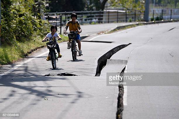 The children bike near the cracks on the ground a day after the 2016 Kumamoto Earthquake on April 15 2016 in Mashiki Kumamoto Japan As of April 15...