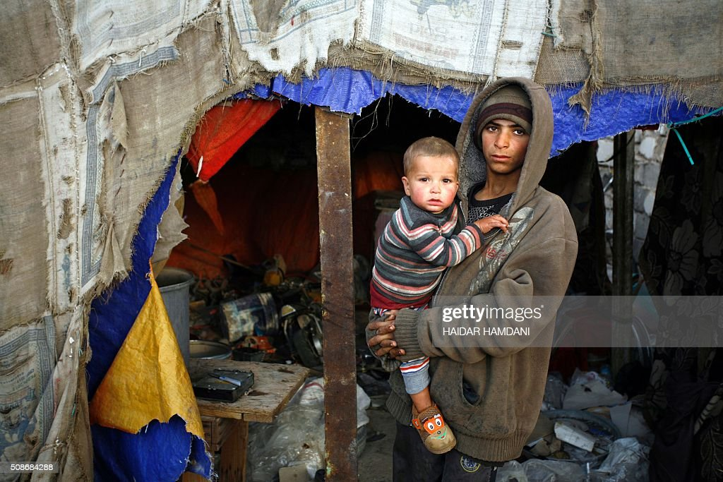 The children of an impoverished Iraqi family, who live in structures made up of scrap metal, stand outside their home in the holy city of Najaf, on February 6, 2016. / AFP / HAIDAR HAMDANI