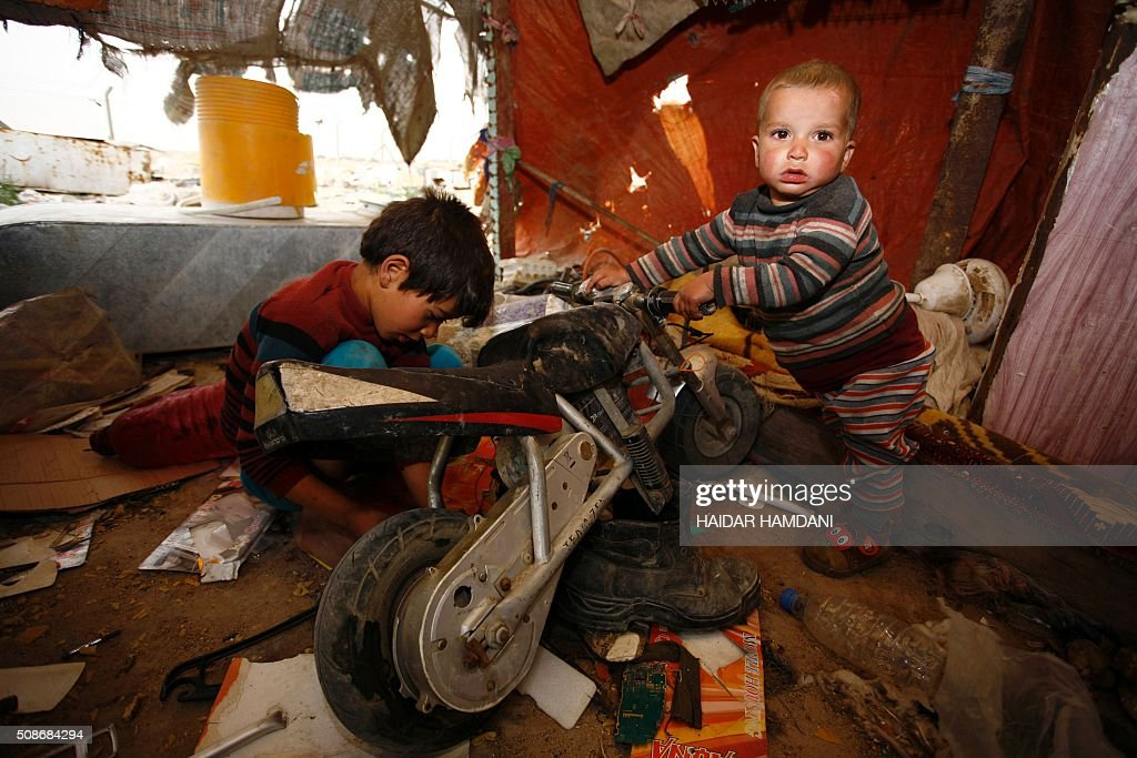 The children of an impoverished Iraqi family, who live in structures made up of scrap metal, play inside their home in the holy city of Najaf, on February 6, 2016. / AFP / HAIDAR HAMDANI