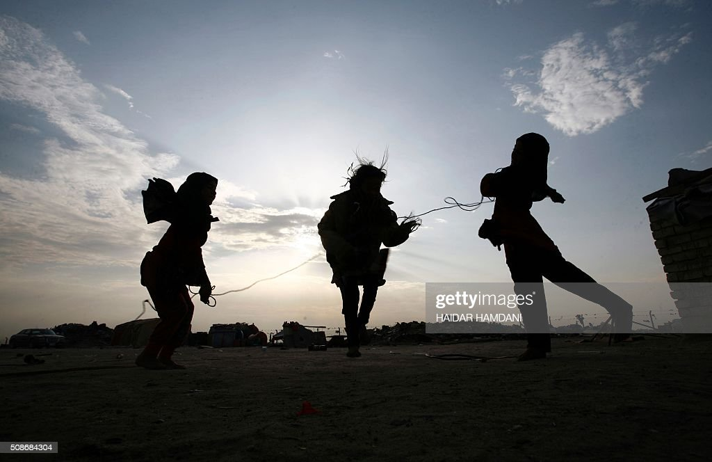 The children of an impoverished Iraqi family, who live in structures made up of scrap metal, play outside their homes in the holy city of Najaf, on February 6, 2016. / AFP / HAIDAR HAMDANI
