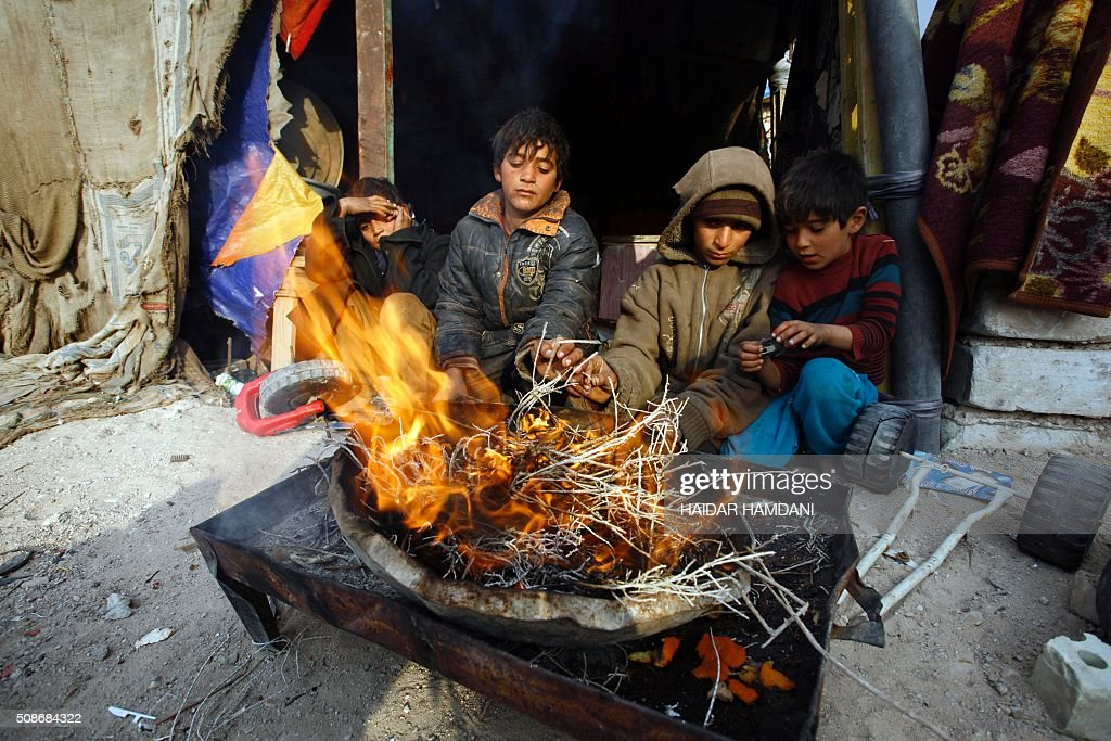 The children of an impoverished Iraqi family, who live in structures made up of scrap metal, sit next to a fire outside their homes in the holy city of Najaf, on February 6, 2016. / AFP / HAIDAR HAMDANI