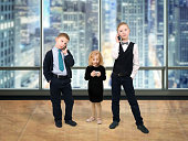 The children of businessmen in the office with gadgets - smartphones