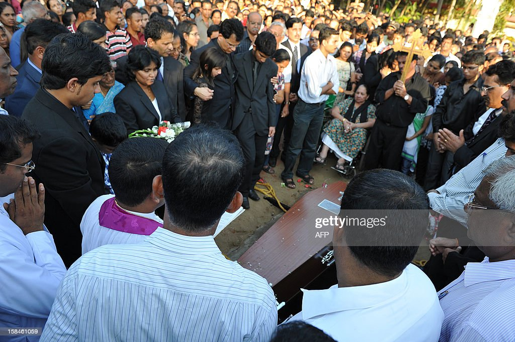 The children of late nurse Jacintha Saldanha, daughter Lisha Saldanha (L) and son Junal Saldanha (R) are consoled by their father Benedict Barbosa (C) during their mother's funeral at The Shirve Church cemetary near Mangalore on December 17, 2012. About 2,000 mourners have packed a Catholic church in southwest India for the funeral of the nurse who was found hanged after taking a hoax call to the hospital treating Prince William's wife. Indian-born Jacintha Saldanha, 46, apparently committed suicide after answering the telephone call from Australian radio DJs to the hospital where the pregnant Duchess of Cambridge was admitted with acute morning sickness.AFP PHOTO/Manjunath KIRAN