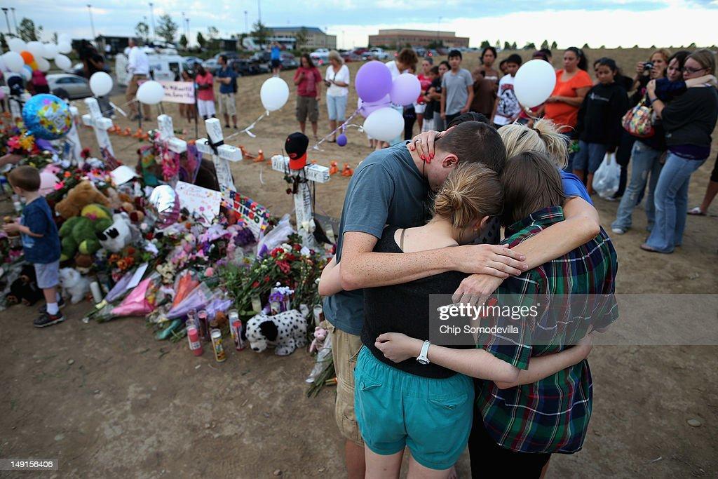 The children of movie-theater-shooting-victim Gordon Cowden embrace one another and pray at the makeshift memorial built across the street from the Century 16 theater July 23, 2012 in Aurora, Colorado. Two of Cowden's teenage daughters were with him in the theater when he was killed. Twenty-four-year-old James Holmes is suspected of killing 12 and injuring 58 others Friday during a shooting rampage at a screening of 'The Dark Knight Rises.'