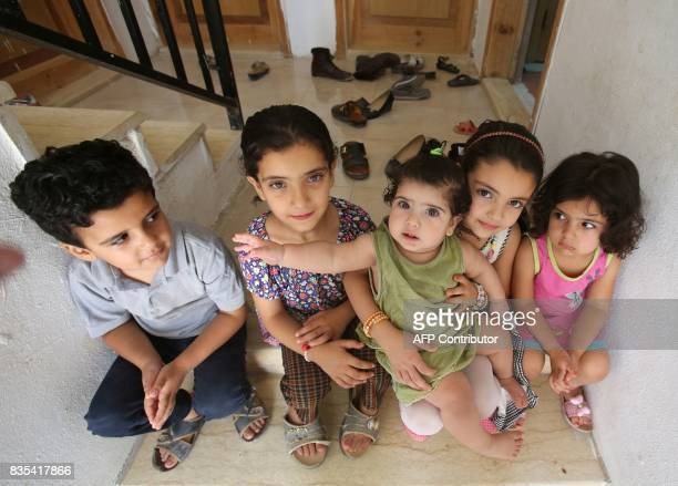 The children of Syrian refugee Mohamed Ghazal pose for a photo on the steps outside a home in the northern Jordanian city of Irbid where they are...