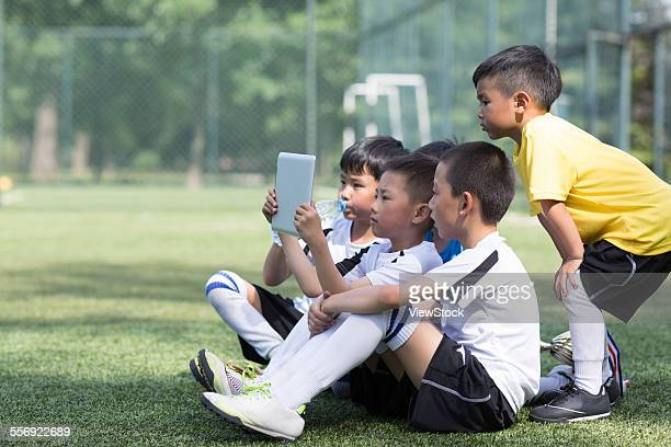 The children took the tablet computer to watch video on the football field