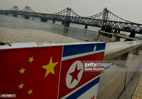 The Chinese and North Korean flags attached to a railing as trucks carrying Chinesemade goods cross into North Korea on the SinoKorean Friendship...