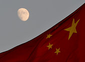 The Chinese flag is seen in front of a view of the moon at Tiananmen Square in Beijing on December 13 2013 China's first lunar rover which entered...