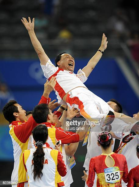 The Chinese team lift Gao Jian director of the gymnastics center of the State General Administration of Sport as they celebrate after winning the...