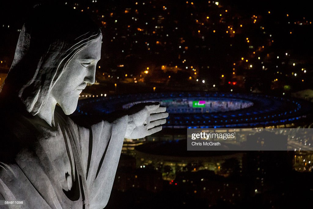 The Christ the Redeemer statue is seen at sunset in front of the Maracana Stadium ahead of the 2016 Summer Olympic Games on July 31, 2016 in Rio de Janeiro, Brazil.