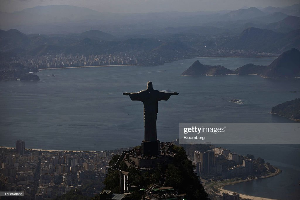 The Christ the Redeemer statue stands on top of Corcovado Mountain in this aerial photograph of Rio de Janeiro, Brazil, on Thursday, July 4, 2013. Brazils shorter-term swap rates fell after a report showed inflation slowed in June more than analysts forecast, damping speculation that the central bank will increase borrowing costs at a faster pace. Photographer: Dado Galdieri/Bloomberg via Getty Images