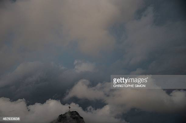 The Christ the Reedemer statue is seen atop the Corcovado mountain surrounded by dark clowds in Rio de Janeiro Brazil on February 07 2015 AFP PHOTO /...