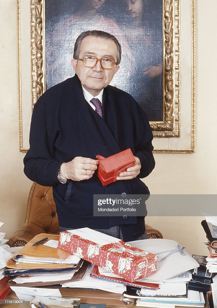 The Christian Democracy party senator <a gi-track='captionPersonalityLinkClicked' href=/galleries/search?phrase=Giulio+Andreotti&family=editorial&specificpeople=221669 ng-click='$event.stopPropagation()'>Giulio Andreotti</a> is standing behind his desk of his office, with a Christmas present in his hands. Italy, 1988..