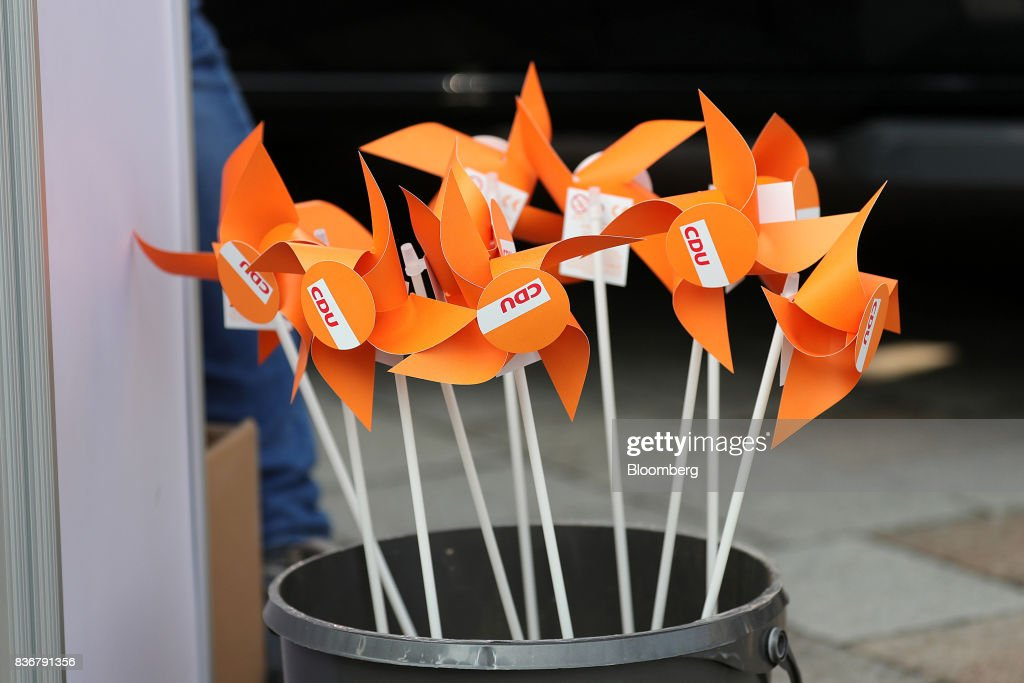 The Christian Democratic Union (CDU) logo sits on pinwheels during a CDU election campaign stop in Saint Peter-Ording, Germany, on Monday, Aug. 21, 2017. Germany's Chancellor and CDU leader Angela Merkel headed out on the campaign trail last week and quickly faced disruption by anti-immigration demonstrators, a reminder that the refugee crisis that sent her popularity plunging in 2016 remains a residual risk. Photographer: Krisztian Bocsi/Bloomberg via Getty Images
