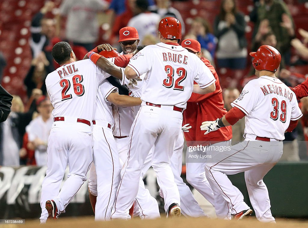 The Cincinnati Reds celebrate with Cesar Izturis #3 after he hit the game winning single in the13th inning to beat the Chicago Cubs 5-4 at Great American Ball Park on April 22, 2013 in Cincinnati, Ohio.