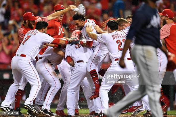 The Cincinnati Reds celebrate with Devin Mesoraco of the Cincinnati Reds after Mesoraco hit a tenth inning walk off home run against the Atlanta...