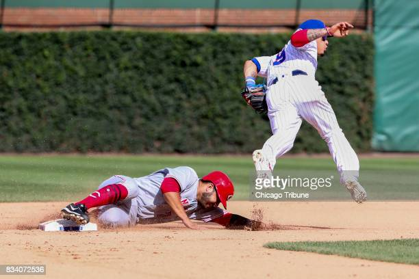 The Cincinnati Reds' Eugenio Suarez steals second base underneath Chicago Cubs second baseman Javier Baez during the eighth inning at Wrigley Field...