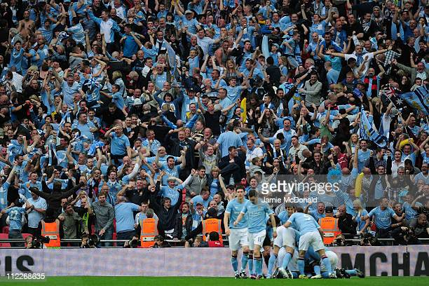 The City fans celebrate after Yaya Toure of Manchester City scored the opening goal during the FA Cup sponsored by EON semi final match between...
