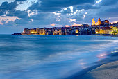 The city of Cefalu in Sicily and the local beach at dusk