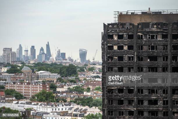 The City of London skyline is seen behind the remains of Grenfell Tower on June 26 2017 in London England 79 people have been confirmed dead and...