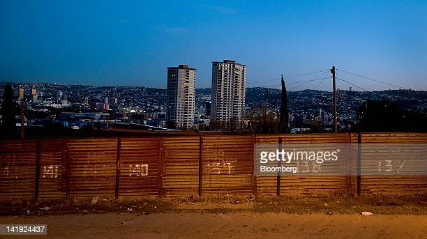 The city of Tijuana Mexico stands beyond the USMexico border fence in San Diego California US on Wednesday March 21 2012 Mexico's peso rose paring...