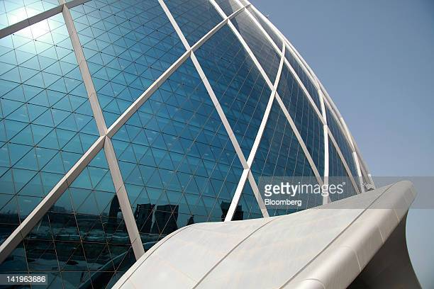 The city skyline is reflected from windows at the headquarters of Aldar Properties PJSC Abu Dhabi's biggest real estate company in Abu Dhabi United...