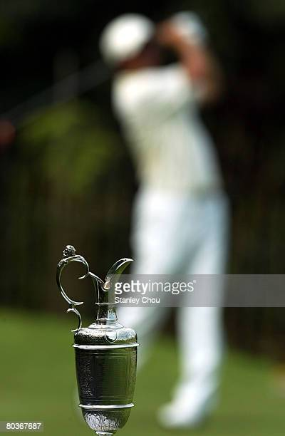 The Claret Jug sits on the foreground while Keiichiro Fukabori of Japan plays his tee shot on the 1st tee during Day One of the Open Championship...