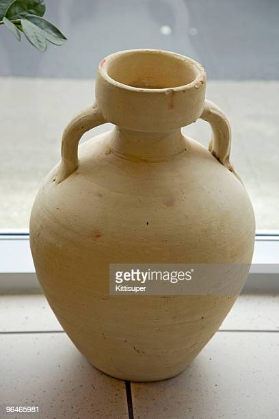 The clay vase costs on tiled to a floor