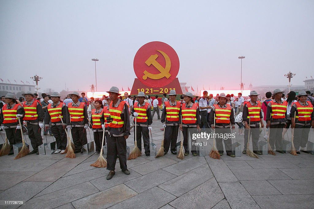 The cleaners stand as a line in front of an emblem of the Communist Party of China (CPC) on the Tiananmen Square on June 30, 2011 in Beijing, China. This year's celebrations will mark the 90th anniversary of the founding of the CPC.