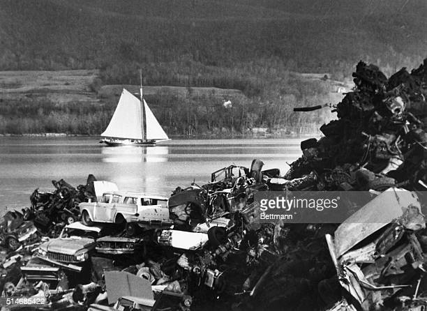 The Clearwater a sloop built to promote the antipollution cause sails down the Hudson River past a junkyard on its way Earth Day activities