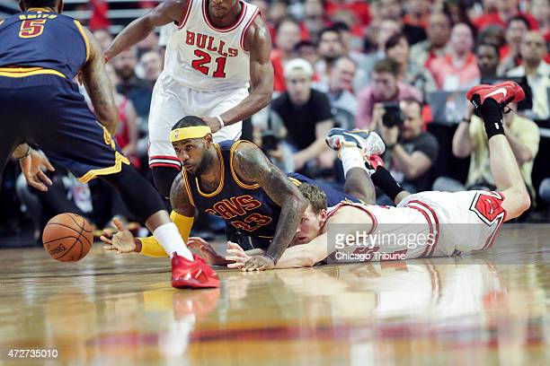 The Cleveland Cavaliers' LeBron James and the Chicago Bulls' Mike Dunleavy fall on the floor while chasing a loose ball during the first half of Game...