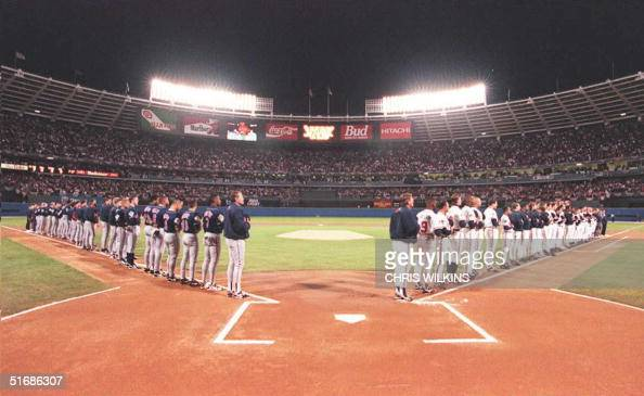 The Cleveland Indians and the Atlanta Braves stand along the baselines as the 'StarSpangled Banner' is sung before the start of the first game of the...