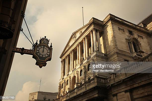 The clock on the Royal Exchange building shows midday in front of the Bank of England on January 8 2009 in London England The Bank has cut interest...