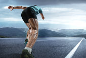 The close up feet and back of man running and training on running track. Advertising image about sport and healthy lifestyle
