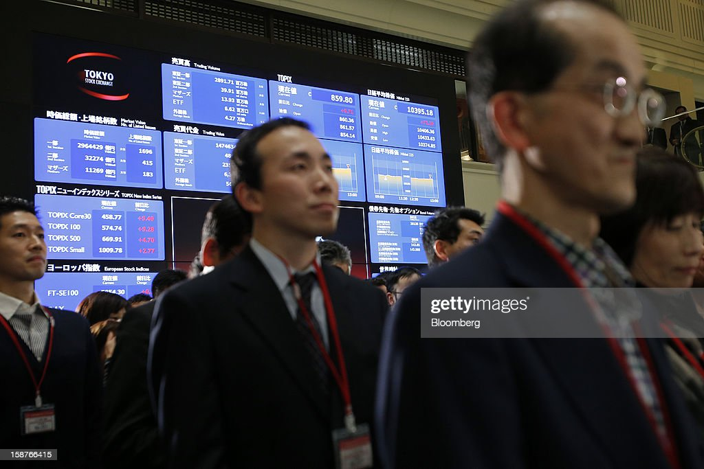 The closing figures of the Nikkei 225 Stock Average, top right, and the Topix Index, second from right, are displayed on an electronic board behind guests during a ceremony marking the last trading day of the year at the Tokyo Stock Exchange (TSE) in Tokyo, Japan, on Friday, Dec. 28, 2012. Japanese stocks rose, with the Nikkei 225 Stock Average capping its biggest yearly advance since 2005, as the yen weakened after consumer prices and industrial production data fueled speculation the central bank will respond to calls for more stimulus. Photographer: Kiyoshi Ota/Bloomberg via Getty Images