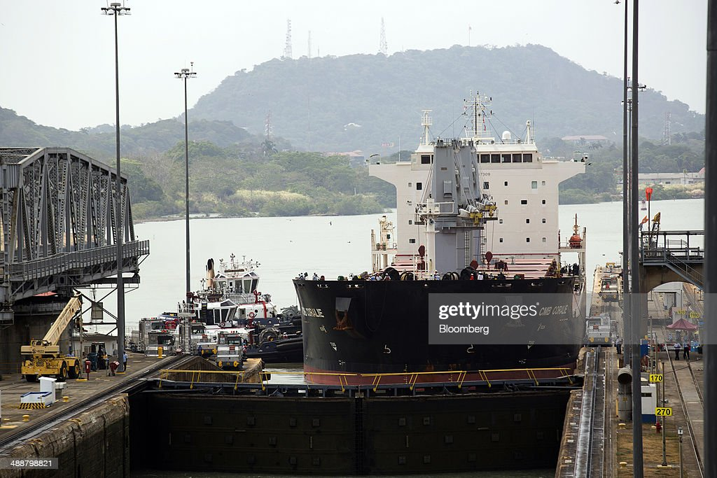 The CMB Coralie dry bulk carrier is gets aligned by tug boats before passing through the Miraflores Locks at the Panama Canal near Panama City, Panama, on Wednesday, April, 23, 2014. Construction projects throughout Panama have remained idle since April 23, when workers walked off the job in an effort to win a 35 percent salary increase. The strike threatens to further delay the canals expansion, designed to accommodate larger ships and help reduce transport costs for commodities such as liquefied natural gas. Photographer: Susana Gonzalez/Bloomberg via Getty Images