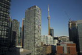 The CN Tower center stands behind residential and commercial buildings in the financial district of Toronto Ontario Canada on Thursday June 30 2016...