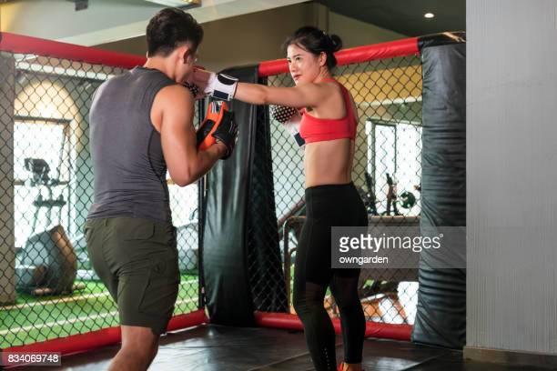 The coach coaching the fitness women in boxing