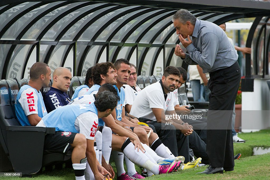 The coach of Brazil's Corinthians, Tite (R) speaks with his reserve players during their Paulista championship football match against Oeste, at Pacaembu stadium in Sao Paulo, Brazil on February 3, 2013. AFP PHOTO/Yasuyoshi CHIBA