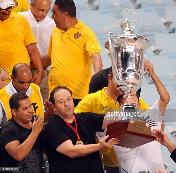 The coach of Esperance de Tunis Nabil Maaloul holds the cup after his team defeated Tunisia's Etoile Sahel 10 during the Tunisian Cup final football...