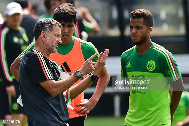 The coach of Mexico's national football team Colombian Juan Carlos Osorio speaks with Giovani dos Santos during a training session in Mexico City on...